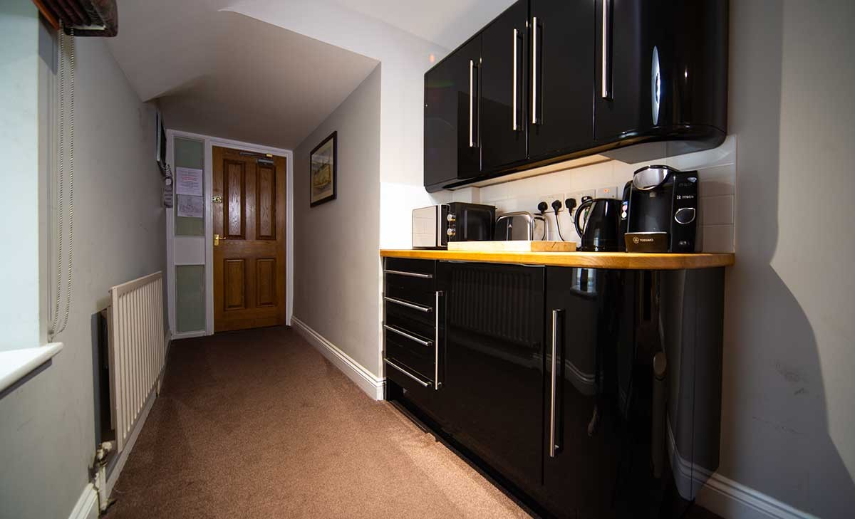 Apartment kitchen area - A photo of a kitchenette, with a wooden bench and black cupboards above and below. On it there is a microwave, a kettle and a coffee machine