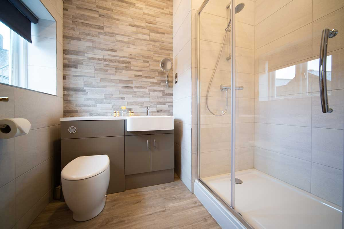 Room 10 bathroom - A photo of a modern bathroom, showing a white toilet, a white modern washbasin and a shower on the right side with glass panels