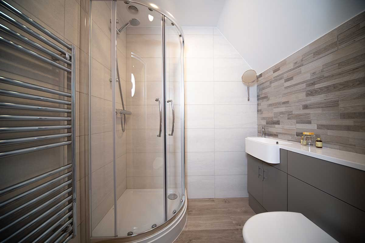 Room 8 bathroom - A photo of a modern bathroom, showing a white toilet, a white washbasin with a cabinet underneath it, and a curved shower with glass panels