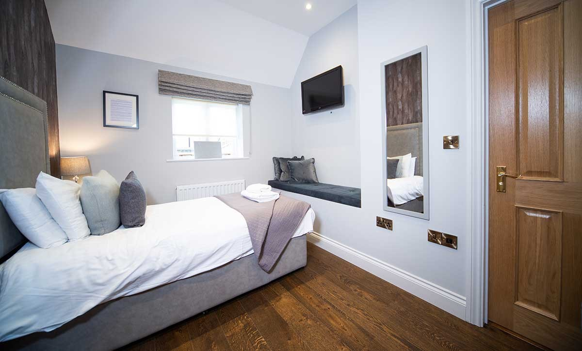 Room 9 bedroom - A photo of the bedroom showing one single bed, with a wooden bedside table, a seating area incorporated to the wall with a blue velvet cushion, a TV above it, and a mirror on the right