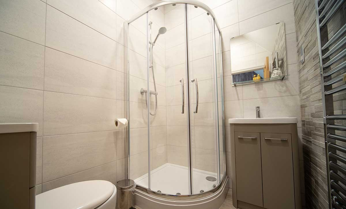 Room 9 bathroom - A photo of a modern bathroom, showing a white toilet, a washbasin with a cabinet underneath it, and a curved shower with glass panels